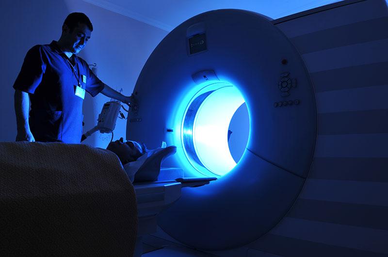 A person putting a person into a MRI